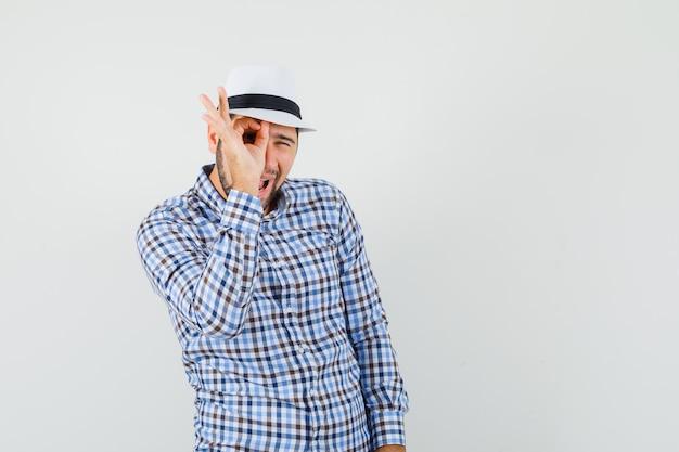 Jovem macho mostrando sinal ok no olho em camisa xadrez, chapéu e olhando curioso, vista frontal.