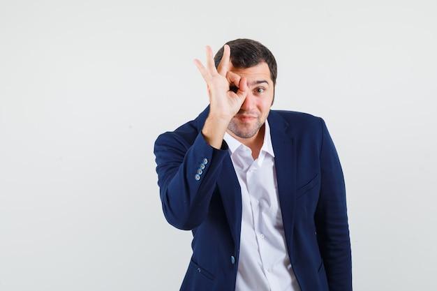 Jovem macho mostrando um gesto de ok na camisa e jaqueta e parecendo confiante