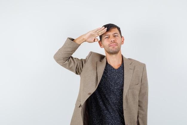 Jovem macho mostrando um gesto de olá militar na jaqueta marrom acinzentada e olhando sério, vista frontal.