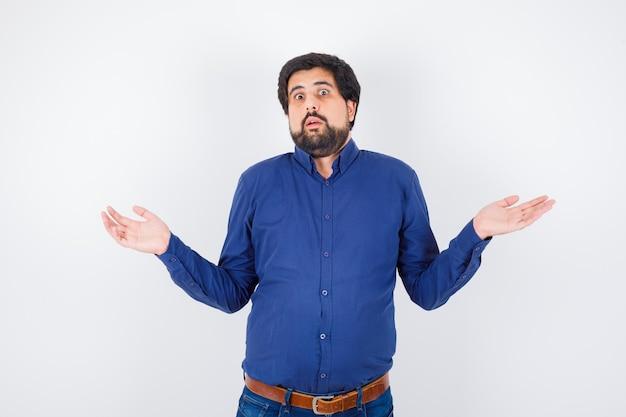Jovem macho mostrando um gesto desamparado em camiseta, jeans e parecendo confuso.