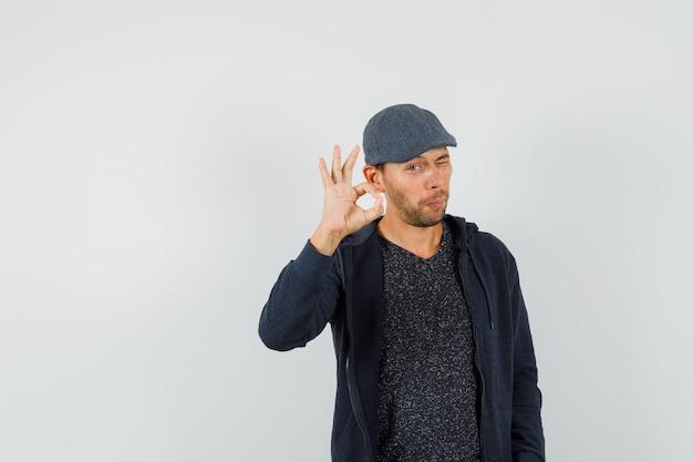 Jovem macho mostrando um gesto ok e um olho piscando em t-shirt, jaqueta, boné, vista frontal.