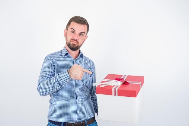 Jovem macho na camisa, apontando para a caixa de presente e olhando confiante, vista frontal.
