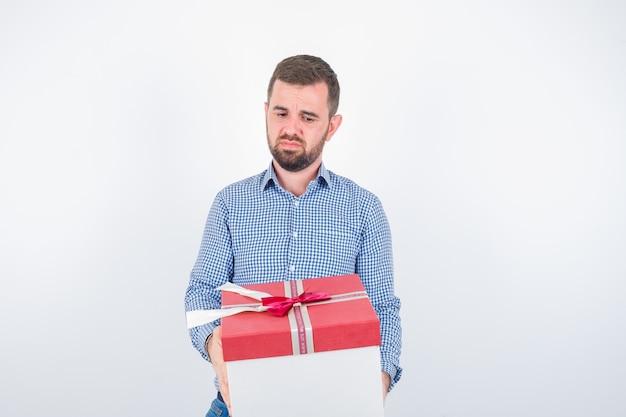 Jovem macho na camisa, segurando a caixa de presente e parecendo desapontado, vista frontal.