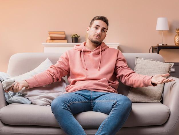 Jovem macho no sofá jogando