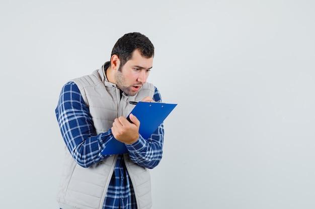 Jovem macho observando algo no papel, na camisa, jaqueta e olhando focado, vista frontal.