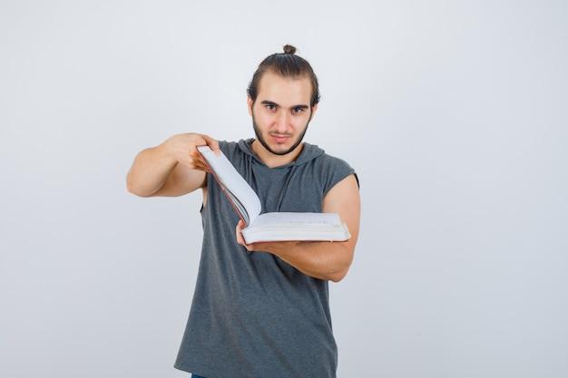 Jovem macho olha através do livro com capuz sem mangas e parece confiante. vista frontal.