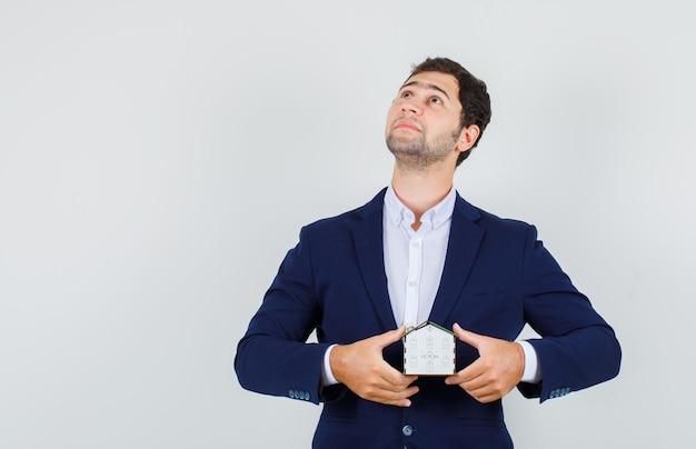 Jovem macho olhando com modelo de casa de terno e olhando pensativo. vista frontal.