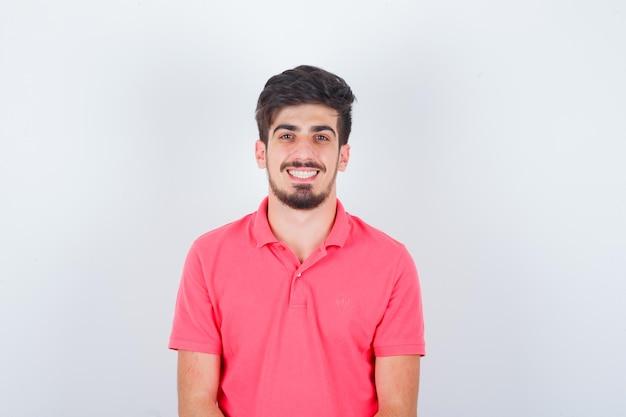 Jovem macho olhando em uma camiseta rosa e olhando alegre, vista frontal.