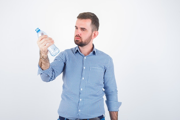 Jovem macho olhando para a garrafa de água de plástico na camisa, jeans e olhando pensativo, vista frontal.