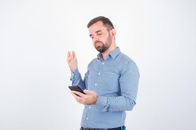 Jovem macho olhando para o celular em camiseta, jeans e parecendo descontente, vista frontal.