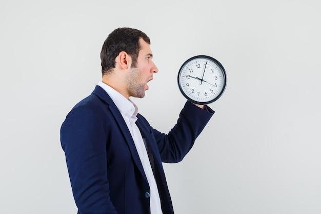 Jovem macho olhando para o relógio de parede com camisa e jaqueta e parecendo surpreso