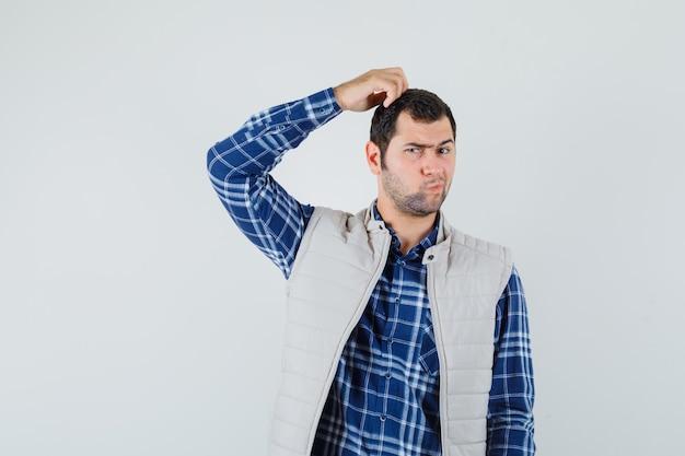 Jovem macho pensando em algo na camisa, jaqueta e parecendo complicado, vista frontal.