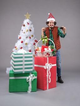 Jovem macho perto de presentes de natal em cinza