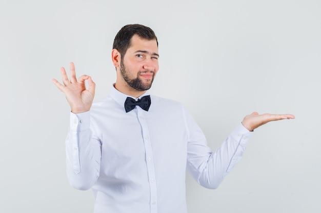 Jovem macho piscando os olhos, mostrando um gesto de ok, espalhando a palma da mão de lado na vista frontal da camisa branca.