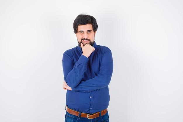 Jovem macho posando enquanto sorria em uma camisa azul royal e parecendo satisfeito, vista frontal.