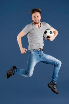 Jovem macho pulando com bola de futebol