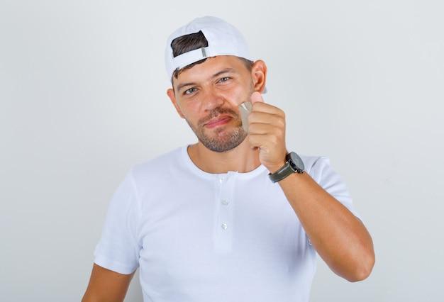 Jovem macho removendo a boca com fita adesiva em t-shirt branca, boné e parecendo com sorte, vista frontal.