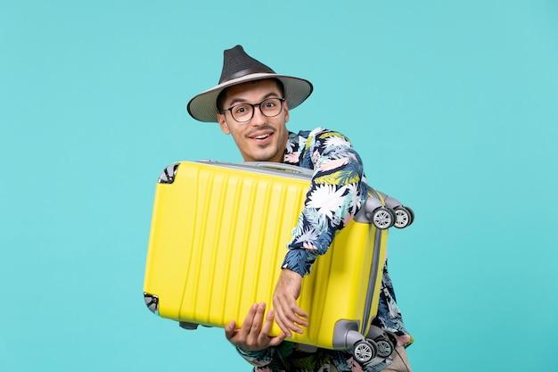 Jovem macho saindo de férias e abraçando sua bolsa no espaço azul