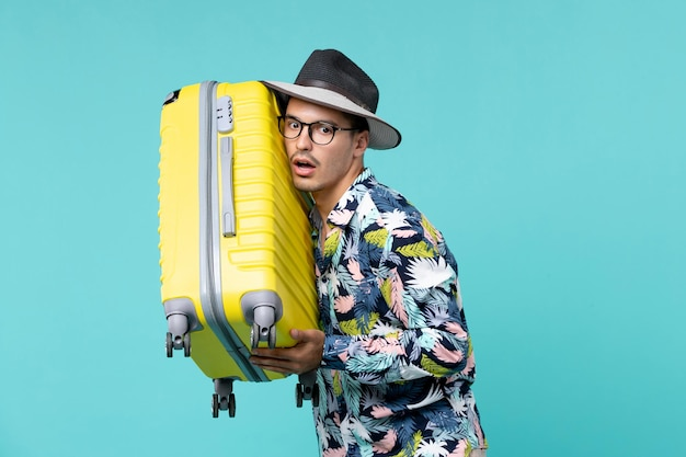 Jovem macho saindo de férias e segurando sua bolsa amarela no espaço azul claro