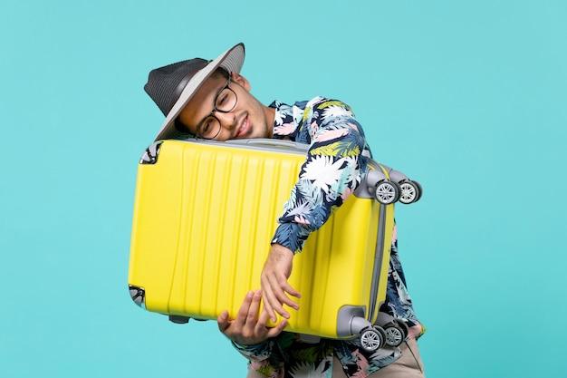 Jovem macho saindo de férias e segurando sua bolsa no espaço azul