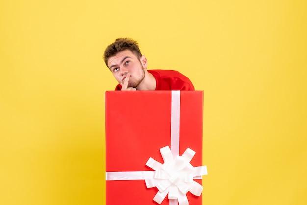 Jovem macho se escondendo dentro da caixa de presente e pensando de frente