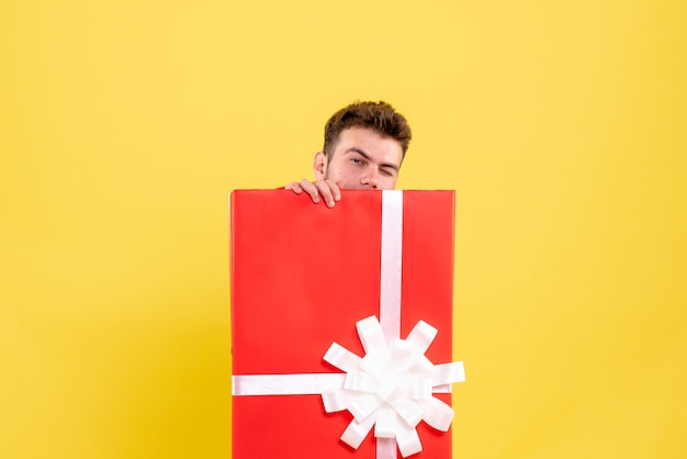 Jovem macho se escondendo dentro da caixa de presente