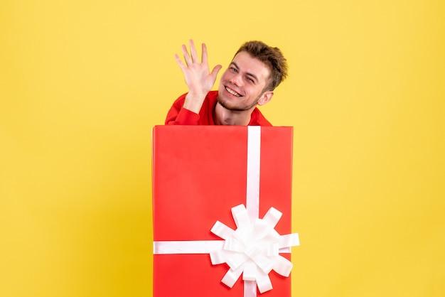 Jovem macho se escondendo dentro da caixa de presentes e sorrindo