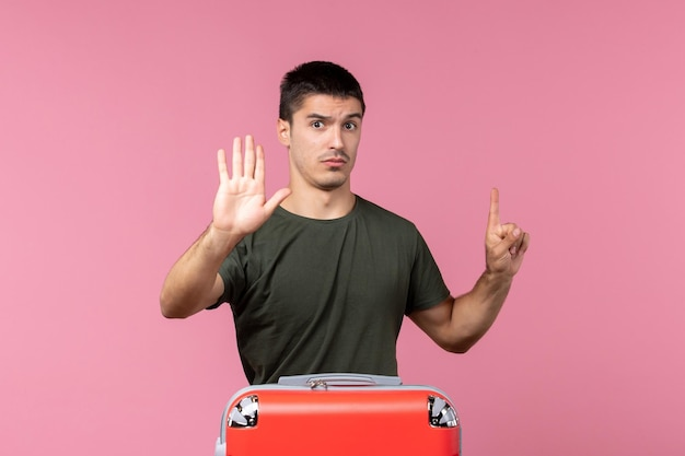 Jovem macho se preparando para as férias com um grande saco no espaço rosa