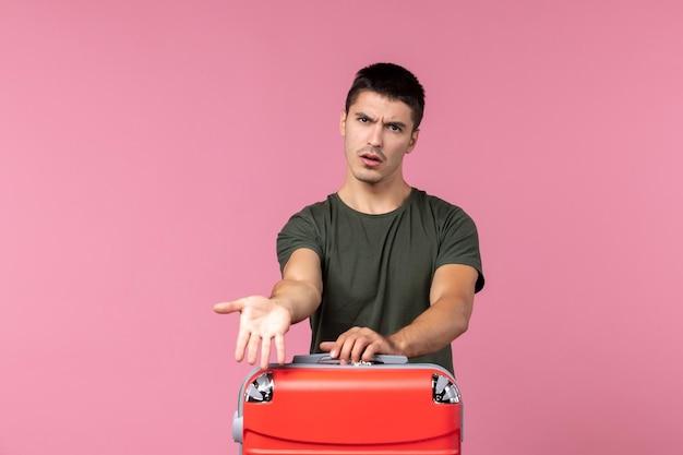 Jovem macho se preparando para as férias no espaço rosa