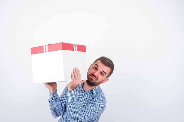 Jovem macho segurando a caixa de presente em camiseta, jeans e parecendo hesitante, vista frontal.