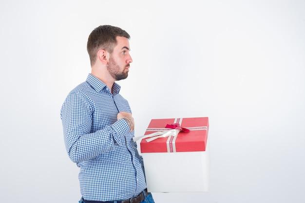 Jovem macho segurando a caixa de presente, mantendo a mão no peito na camisa e olhando perplexo, vista frontal.