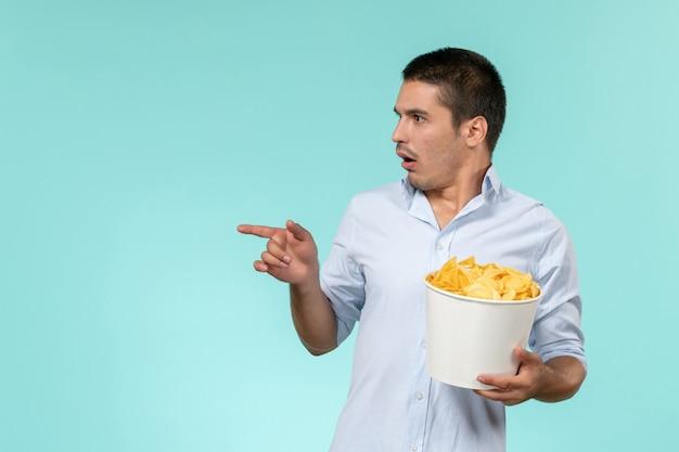 Jovem macho segurando a cesta com batatas fritas e assistindo filme na mesa azul