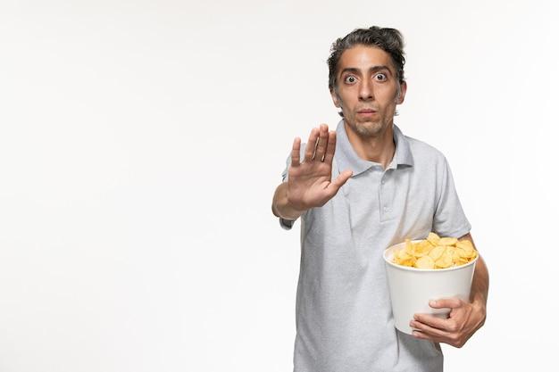 Jovem macho segurando a cesta com batatas fritas e pedindo para parar na superfície branca