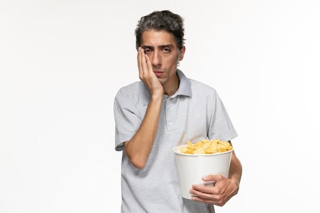 Jovem macho segurando a cesta de frente com batatas fritas deprimida na superfície branca