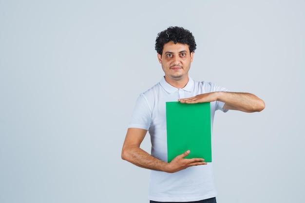 Jovem macho segurando a prancheta em camiseta branca, calça e elegante. vista frontal.
