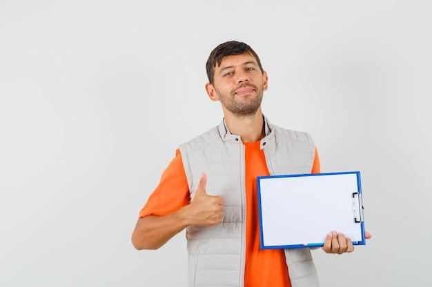 Jovem macho segurando a prancheta, lápis, aparecendo o polegar em uma camiseta, jaqueta e parecendo feliz. vista frontal.