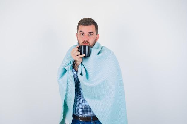 Jovem macho segurando a taça enquanto olha para a câmera em camisa, jeans, cobertor e olhando sério. vista frontal.