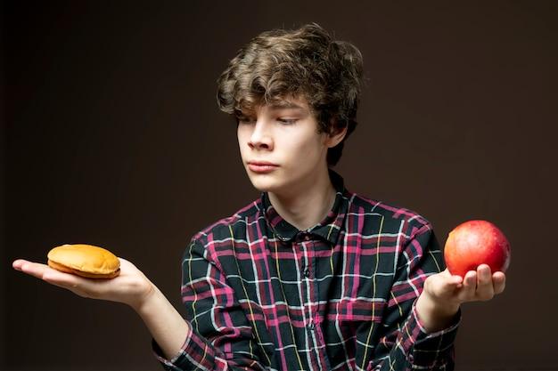 Jovem macho segurando e escolhendo entre maçã ou hambúrguer b