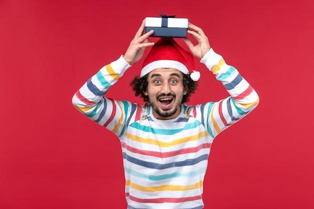 Jovem macho segurando feriado presente na parede vermelha emoção de feriado de ano novo