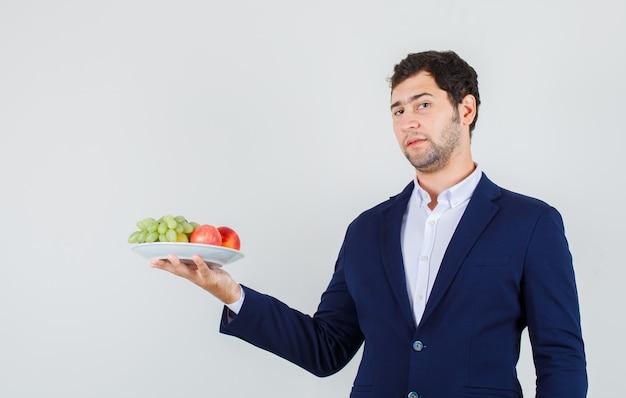 Jovem macho segurando frutas no prato de terno e parecendo confiante. vista frontal.
