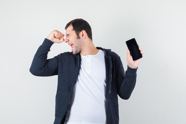 Jovem macho segurando o celular em t-shirt, jaqueta e parecendo feliz. vista frontal.
