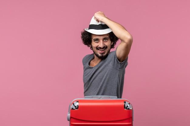 Jovem macho segurando o chapéu e se preparando para as férias no espaço rosa