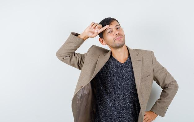 Jovem macho segurando o dedo na testa em jaqueta marrom acinzentada, camisa preta e parecendo estranho. vista frontal.