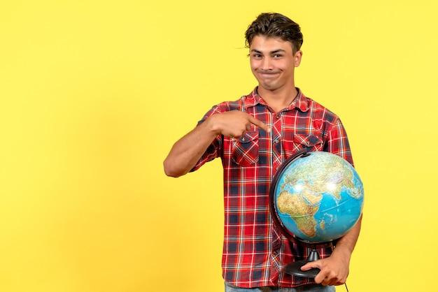 Jovem macho segurando o globo terrestre na cor do modelo masculino de fundo amarelo
