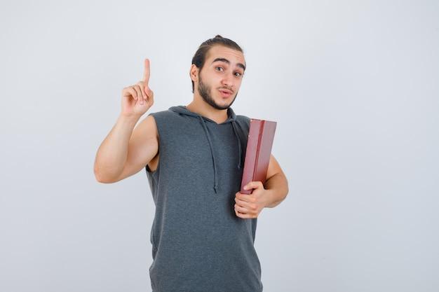 Jovem macho segurando o livro enquanto aparecendo apontando para cima com um capuz sem mangas e olhando confiante, vista frontal.