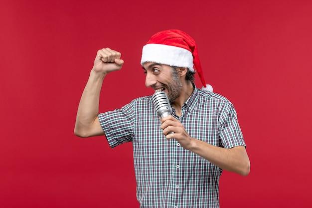 Jovem macho segurando o microfone no fundo vermelho