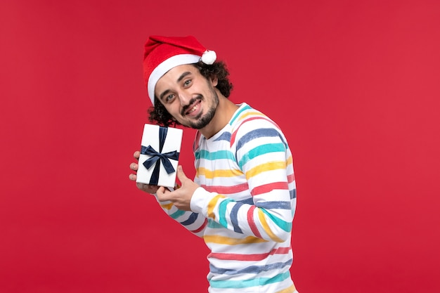 Jovem macho segurando o presente de ano novo de frente na emoção de ano novo de feriado de fundo vermelho