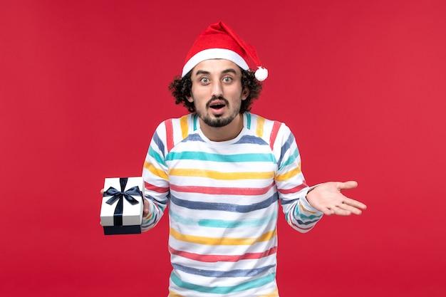 Jovem macho segurando o presente de ano novo de frente no fundo vermelho, feriado vermelho, ano novo
