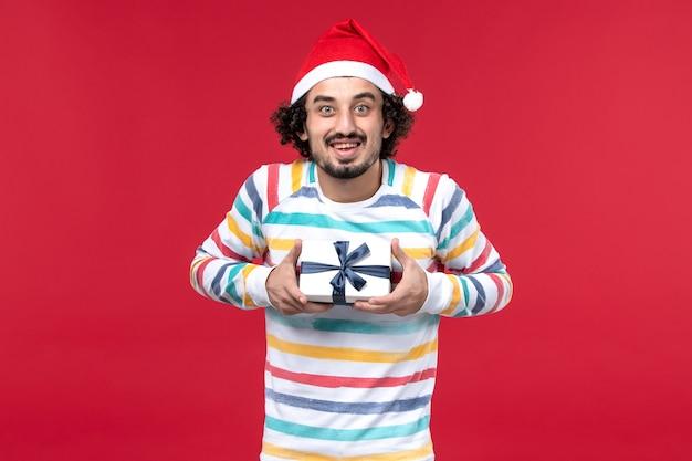 Jovem macho segurando o presente de ano novo de frente no fundo vermelho, feriados, ano novo vermelho