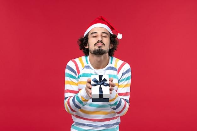 Jovem macho segurando o presente de ano novo nas emoções de ano novo de férias de fundo vermelho
